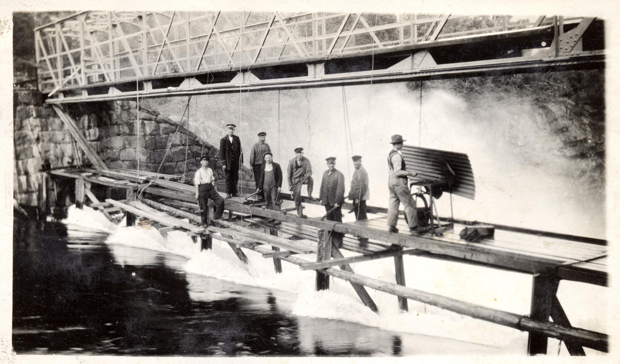 Slusevoktere jobber med vedlikehold av dammen i Vrangfoss. Alle har uniformslue med unntak av smeden som jobber ved den mobile essa.