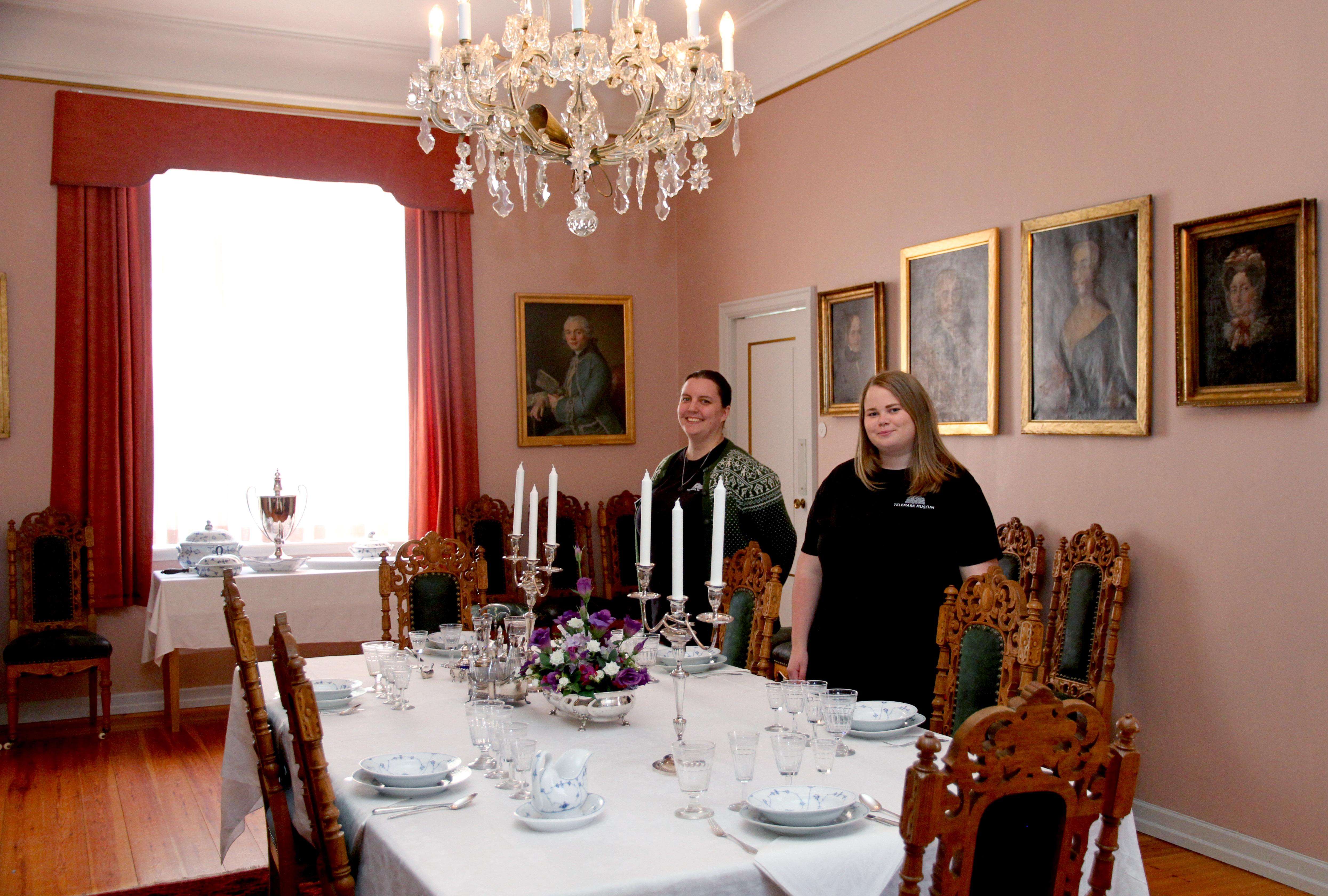 KUNNSKAPSRIKE: Telemark Museum er heldige som kan invitere gjester til flinke sommerverter. Her er Kristine Andersen og Amalie Haugen Røimål ved dekket bord i spisestuen. Familien Aall vokter det hele fra veggplass.