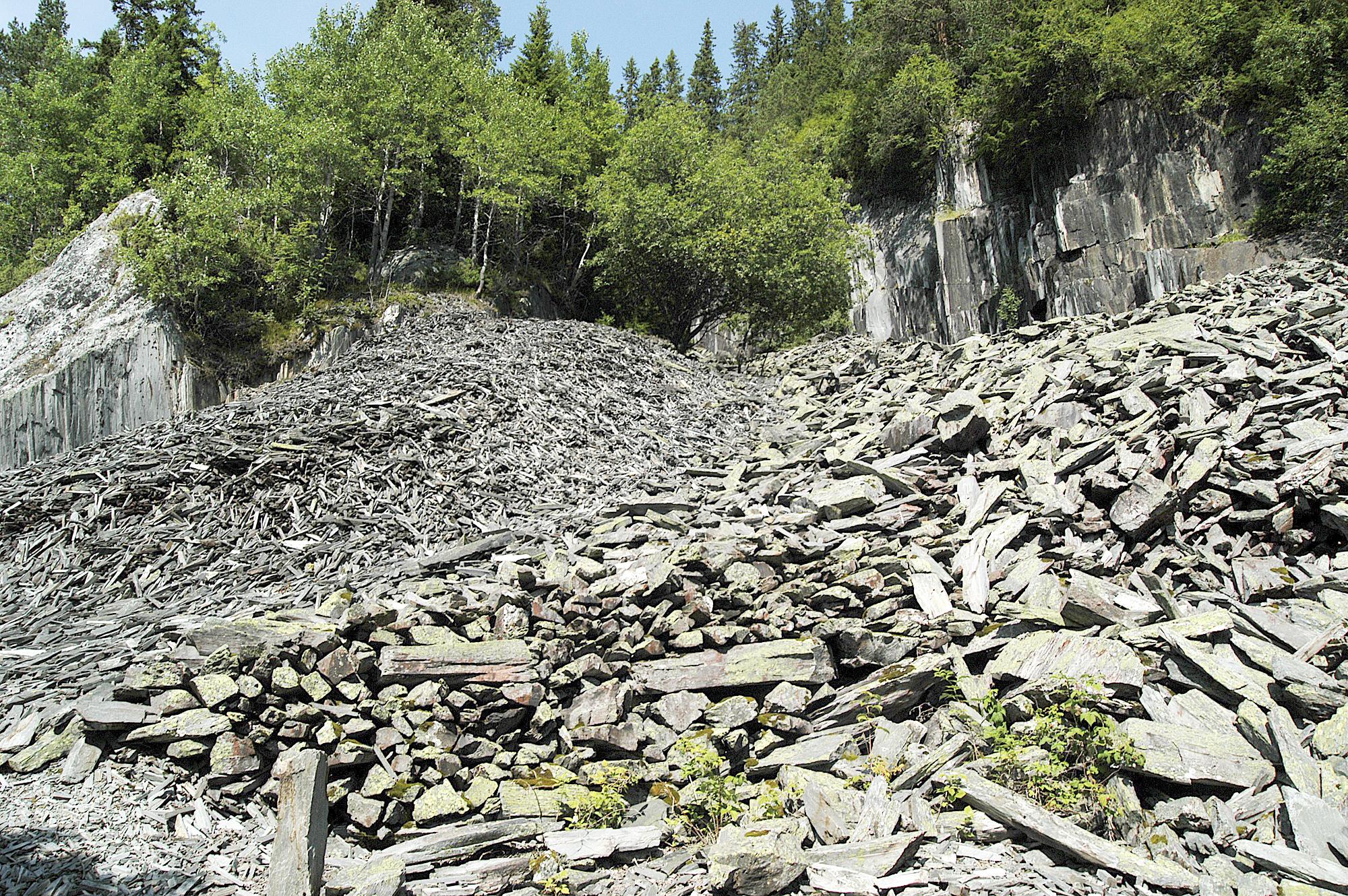 Et av steinbrudda ved Eidsborg slik det ser ut i våre dager. Avfallet etter arbeidet i steinberget ligger i hauger, uslehauger. Det går sti fra Vest-Telemark museum inn til steinberget.