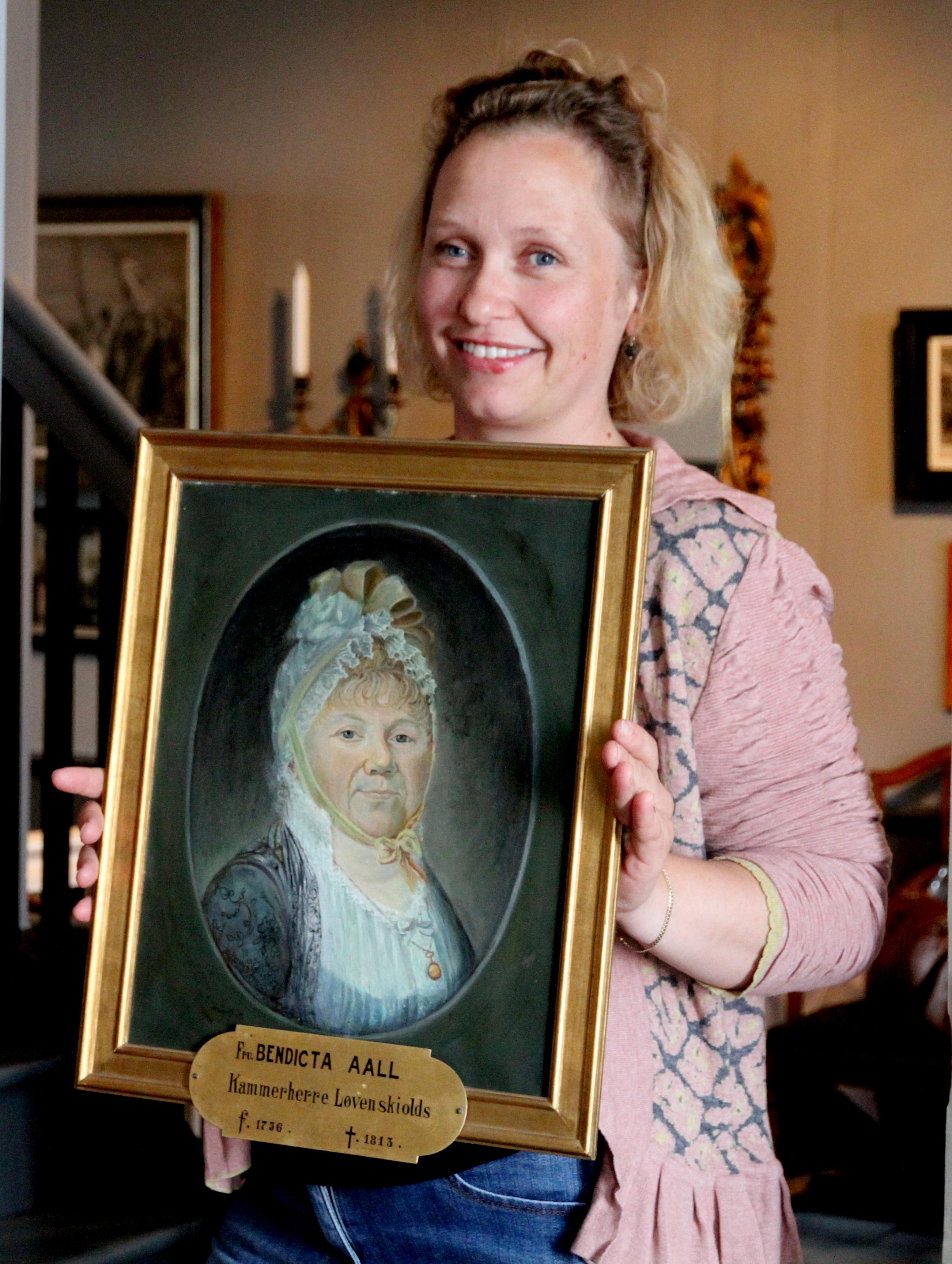 Christine Hermansen ved Telemark Museum holder et maleri av Benedicta, tanten til Niels Aall.   Foto: Kristin Berge, Telemark Museum
