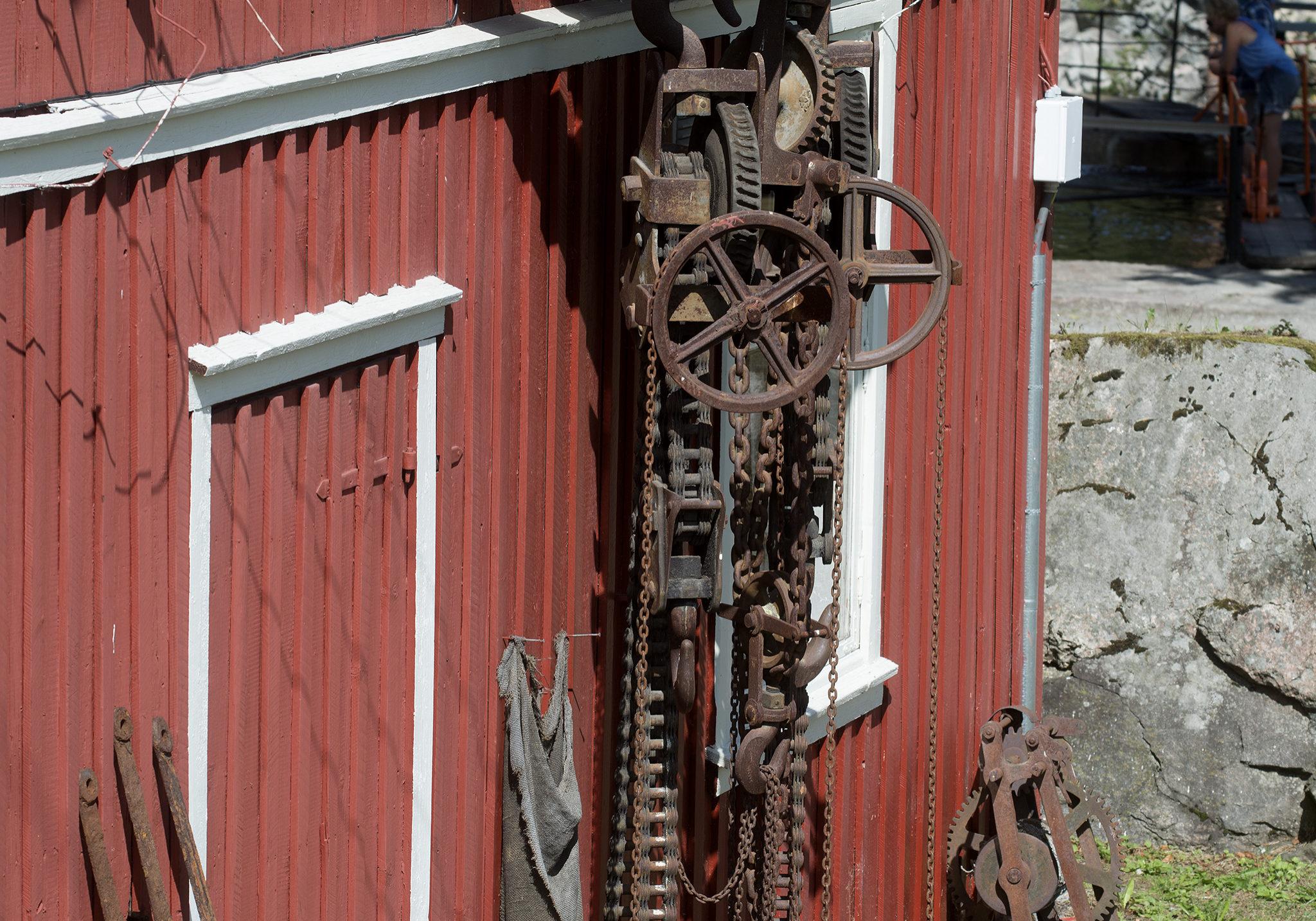 Taljer som henger på smieveggen, ble tidligere brukt til å løfte de ca. 10 tonn tunge sluseportene.