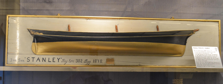 """""""Stanley"""" som var eiet av flere i et partsrederi med blant andre Porsgrunnsrederen Nicolai Friis, hadde en lengde på 130 fot, en bredde på 29 og dypgang på 10,8. Hun var blitt bygget ved Johan Jeremiassens verft i Porsgrunn i 1878 – der vi i våre dager finner Minneparken. """"Stanley"""" var på 313 bruttotonn, og fraktet blant annet mahogany.  Denne modellen er det selveste statsminister Gunnar Knudsen som har laget."""