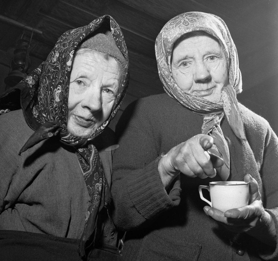 """Dalen i Telemark, Februar 1955. Ingerine (th) og Gurine Schevenius (83 og 81 år gamle) bor alene på plassen Roi eller Rui i Dalen i Telemark. Tiden har stått stille på denne lille plassen høyt oppe i fjellheimen. Her de to sammen. Ingerine peker på fotografen og spør: """"Er det springvatn i Kristianaia?"""" Foto: Aage Storløkken / Aktuell / Scanpix"""