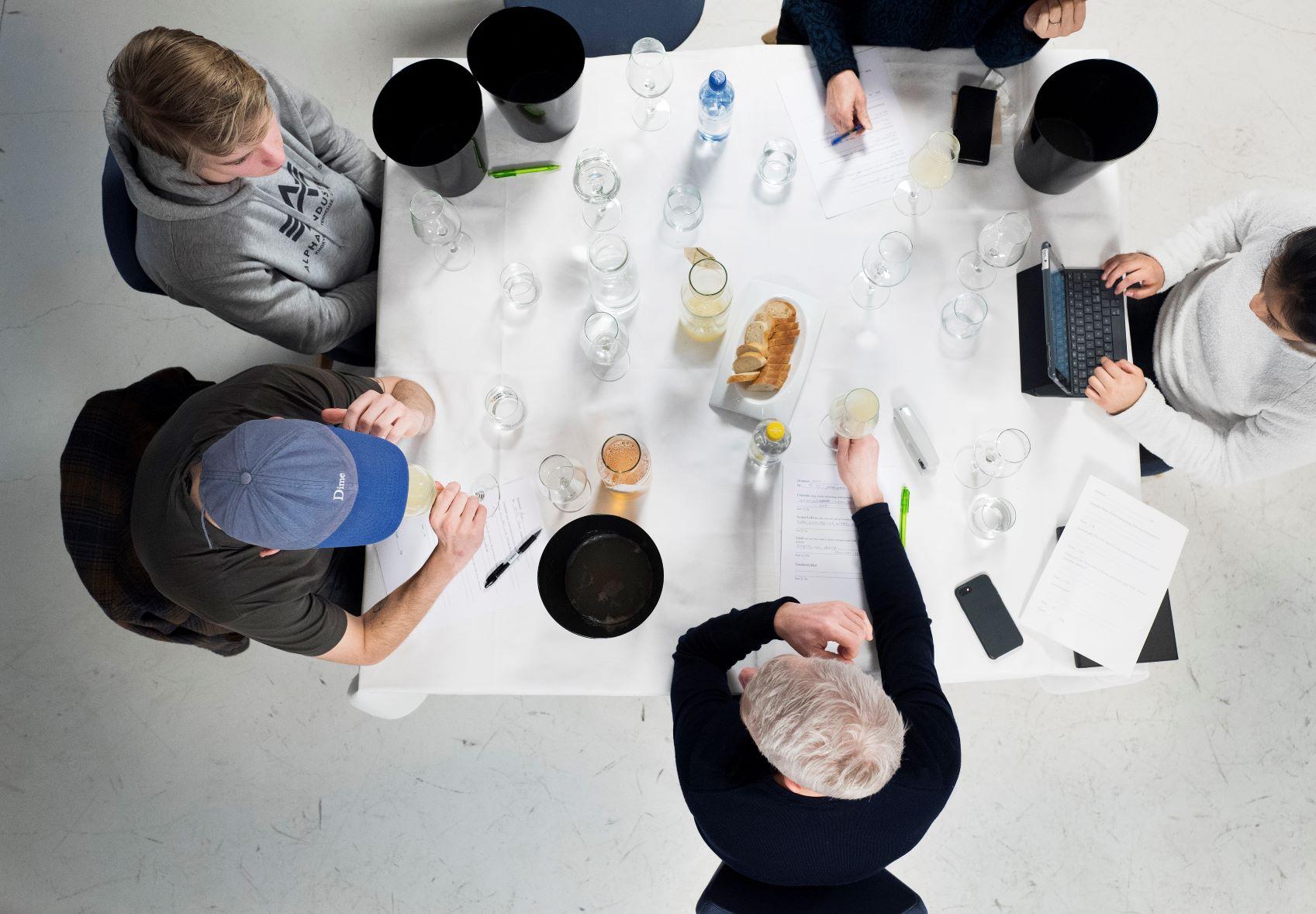 Smakspanelet både spytter ut og noterer ned under smakingen. Vann til å skylle munnen med står på bordet. Alt er i rute. Foto: Fredrik Solstad/HANEN