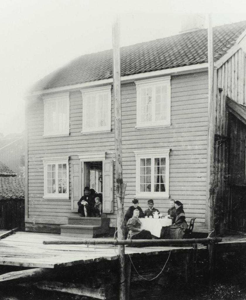 Barndomshjemmet i Søndre-Strandgate i Langesund. Faren, Hans Jakob i inngangen, mannen ved bordet er nok eldstebror Peter, og sittende helt til høyre ser vi moren, Nielsine