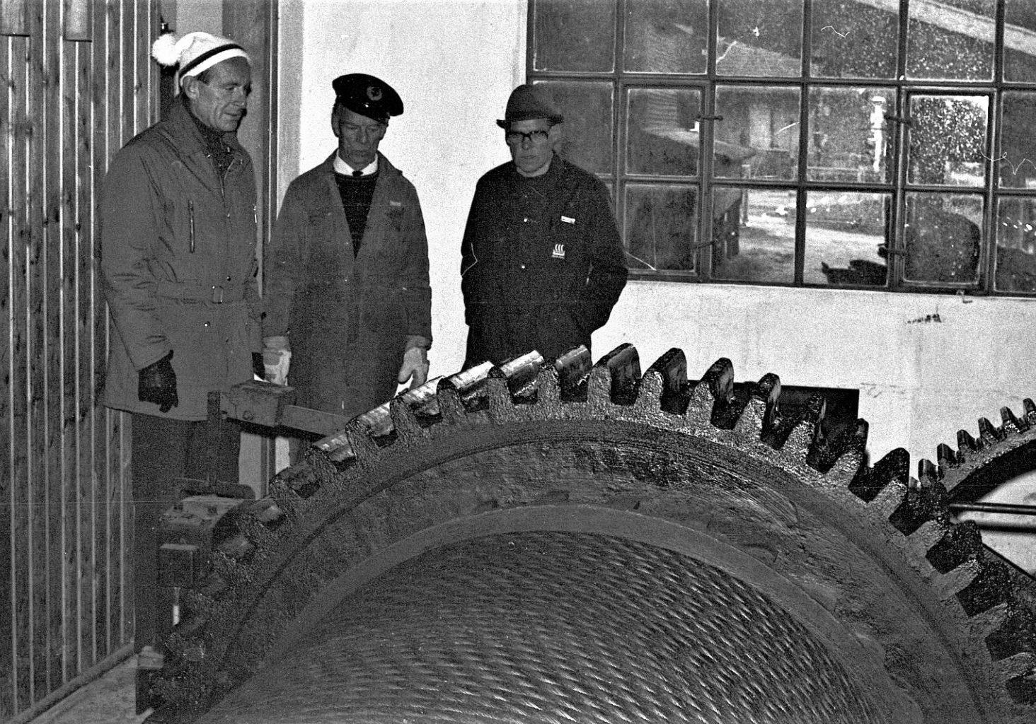 Solide dimensjoner: Maskinhuset på Tinnoset inneholder bl.a. elektrisk drevne tromler med slippwire og tannhjul. Alt er dimensjonert for å kunne trekke Nordens største innlandsferje, MF Storegut, opp på slippen. Her fra inspeksjonen av en skade på lageret til vinsjtrommelen på 1970-tallet. «Sjefsmaskinist» Brodtkorp i midten. (Foto: NIA).
